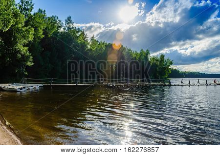 Beautiful sun-drenched coast of forest lake with a pier and white boats on a background of blue sky