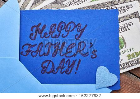 Dollars near Father's Day card. Blue fabric heart on card. Financial support for dad.