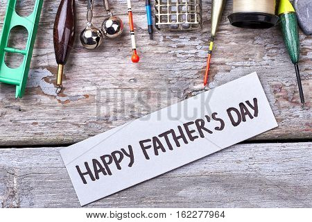 Happy Father's Day greeting paper. Fishing tackle near card. Relaxing weekend for dad.