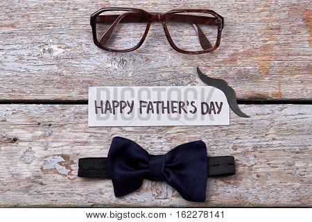 Glasses, mustache and bow tie. Spectacles and card on wood. Father's Day fashion.