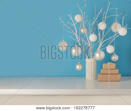 Vase in white knitted cover with white branches and Christmas toys. Gifts are Packed in Kraft paper.