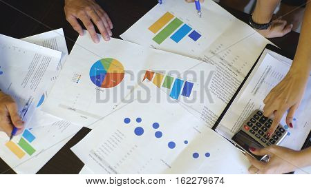 Businessman and woman discussing on stockmarket charts in office, close up