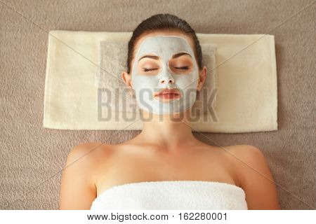 Spa concept. Young woman with nourishing mask on face relaxing in spa salon