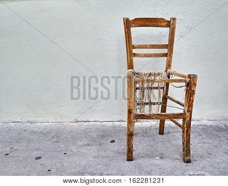 old warn coffee shop chair on blank wall
