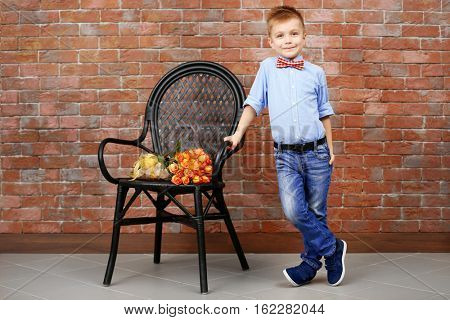 Cute boy and chair with bouquet of beautiful flowers near brick wall
