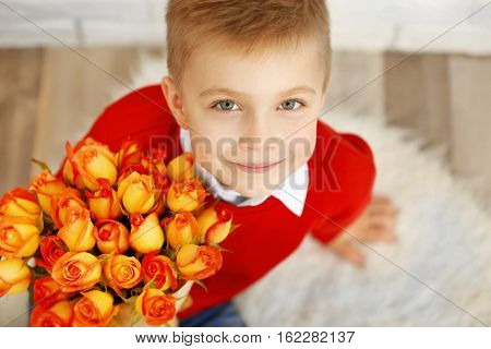 Cute boy with bouquet of beautiful flowers, close up