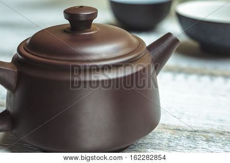 Traditional Teapot from Yixing clay for Chinese tea ceremony on rustic wooden background Close up image