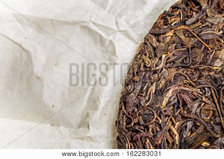 old Shen puerh chinese fermented tea on papyrus paper background with copyspace. Top view