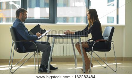 beautiful businesswoman in black dress asking questions at the interview