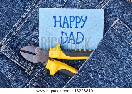 Dad's greeting paper and jeans. Pliers on pocket near card. How to congratulate father.