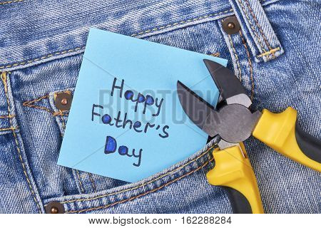 Pliers near Father's Day card. Jeans pocket with pliers. Masculine present for best daddy.