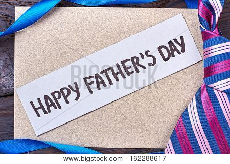 Father's Day card near tie. Ribbon and greeting card. Present for dear daddy.