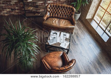 Top view. Leather armchair near cozy couch. Table with laptop and papers is between them