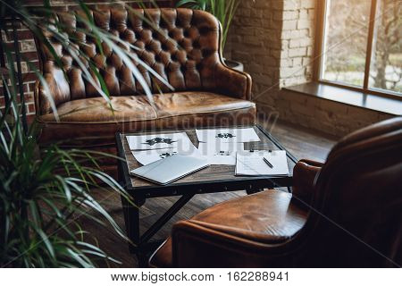 Room with furniture. There are rorschach test, laptop and paper on table