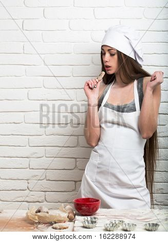 Pretty girl or beautiful woman cute chef cook or baker with long hair in white hat and apron eats cookie on white kitchen wall