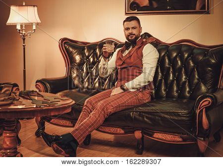 Extravagant stylish man with glass of whisky sitting on classic leather sofa in gentleman club