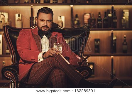 Extravagant stylish man with whisky glass sitting on armchair in gentleman club