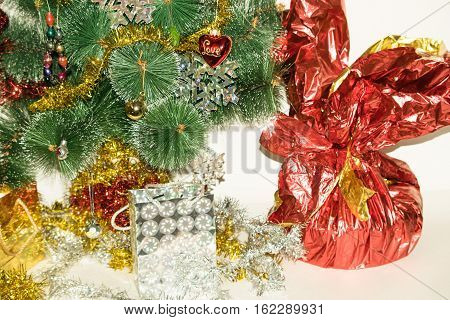 Christmas tree decorated with bright colorful toys snowflakes. Under the tree are gifts of silver and gold gift bags and gift in a red-golden shiny packaging