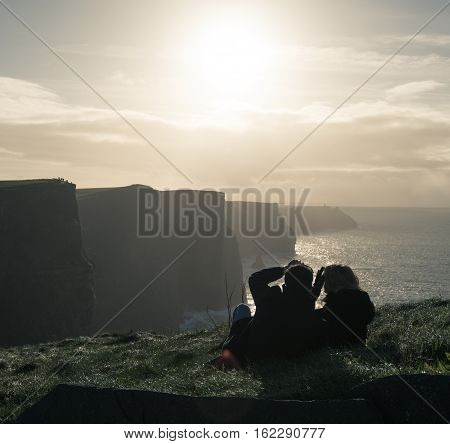 County Clare Ireland - November 10 2016: Young couple laying on the grass and enjoying the view at the Cliffs of Moher