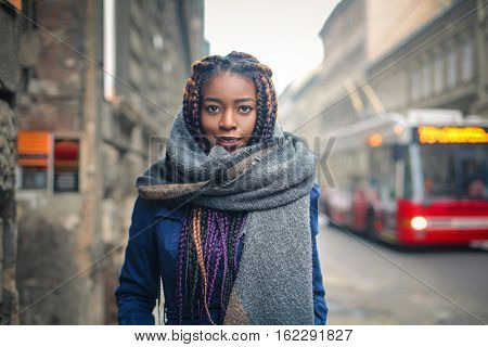 Black girl with a huge scarf is walking on a street with a trolley bus.