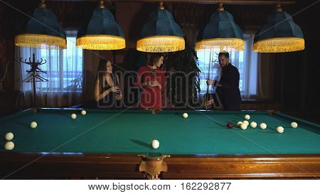 a man plays Billiards and two young beautiful women watching the game, a man demonstrates skill in the game of Billiards