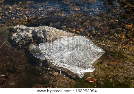Piece of ice on stone closeup in mountain river waters in winter