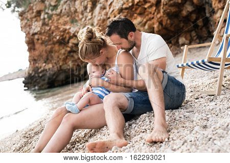 Beautiful young family with their baby son at the beach, enjoying time at seaside, hugging.