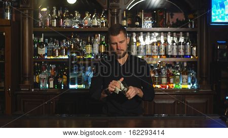 bartender is wiping a glass, Attractive smiling young bartender standing and wiping glasses in pub