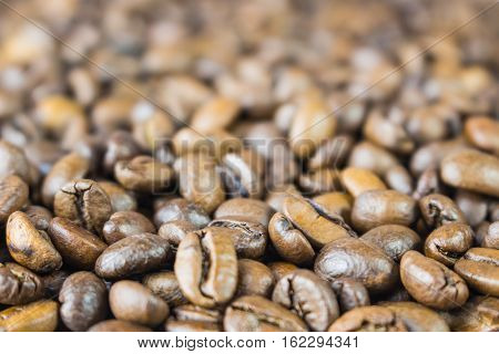 Coffee beans on grunge wooden background on the table closeup side view