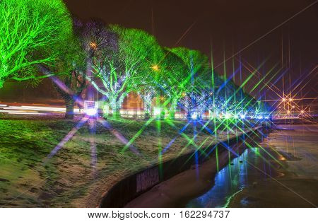 New Year illumination on and between trees next to frozen river and street star filter