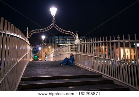 Dublin Ireland - November 07 2016: Lonely beggar at the Ha'penny Bridge at night