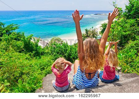 Happy family travel - mother baby son daughter sit on cliff steps look at sea surf on white sand beach. Active parent lifestyle people outdoor activity on summer vacation with child on Bali island