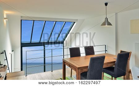 Dining table in modern duplex with large windows and sea