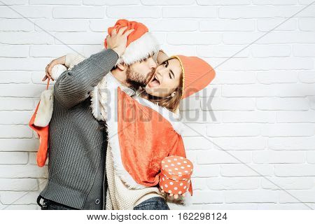 Young happy kissing Christmas couple in red santa claus hats of man with gift box and pretty sexy girl or beautiful woman winking on white brick wall