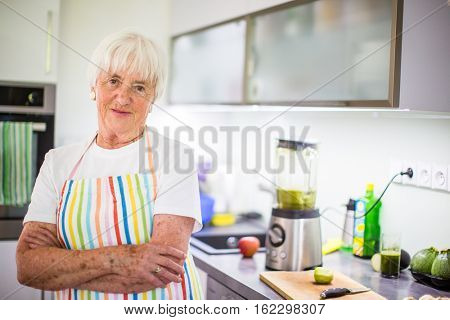 Senior woman/grandmother cooking in a modern kitchen (shallow DOF; color toned image)