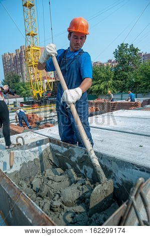 Tyumen, Russia - July 31, 2013: JSC Mostostroy-11. Construction of 18-storeyed brick residental house at the intersection of streets of Nemtsov and Tsiolkovsky. Worker kneads solution for bricklayers