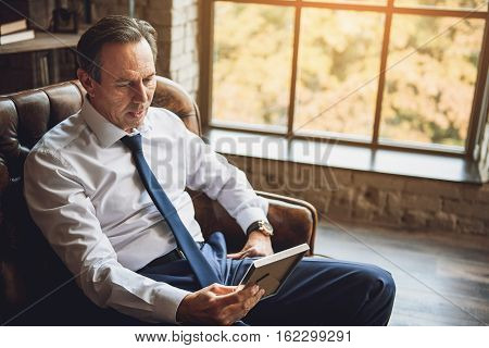 Concentrating businessman is sitting in room. He is holding a photo and looking at it with attention