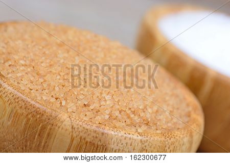 Bowl with beige and white sugar on table