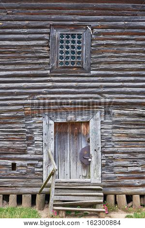 Facade of an old rickety wooden building with a door and window