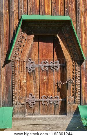 Wooden door decorated with carvings and strengthened with metal plates