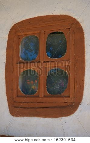 Window in the rural house in Ukraine in the second half of the nineteenth century. In the reflected sky trees flowers