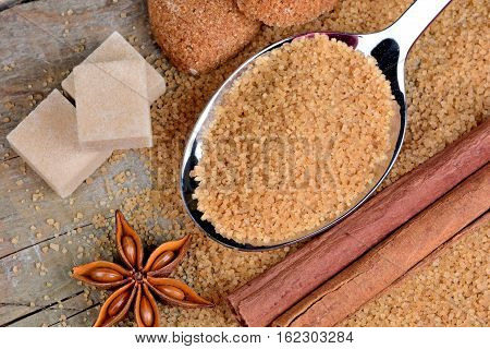 Sugar in a spoon and anise star with cinnamon on table