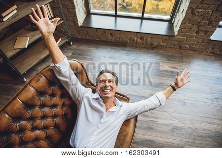 I want to hug all the world. Happy businessman is lying with bright smile
