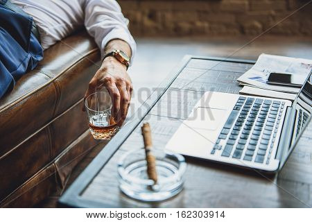 Businessman is lying on couch and holding glass with amber whiskey. Close up of male arm