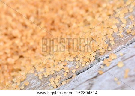 Beige sugar on wooden table close up