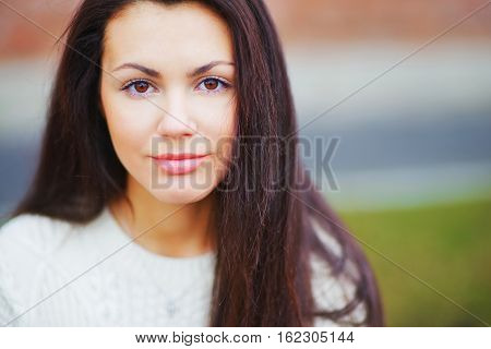 Portrait of pretty long-haired girl brunettes with beautiful brown eyes in sunny day closeup on blurred background.