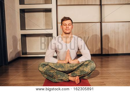 the man in the Lotus position, young man doing yoga exercise in special studio