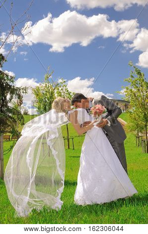 A married couple bride and groom about to kiss in sunshine on a beautiful waterfront city