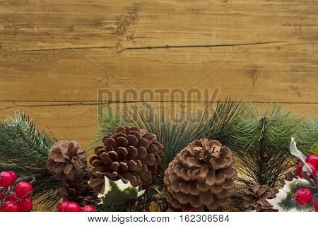 Old fashion Christmas background Garland with pine cones and red holly berries on weathered wood background with copy space for your message