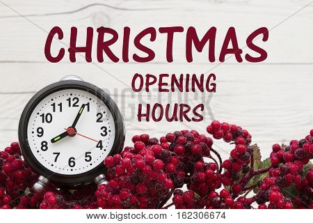 Old fashion Christmas store message Frost covered red holly berries with an alarm clock on weathered wood background with text Christmas opening hours